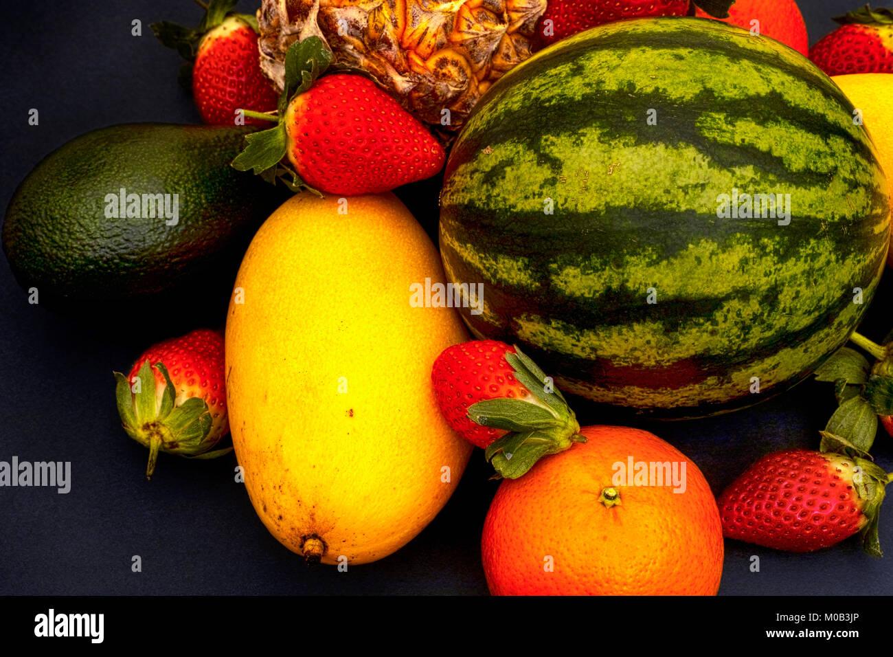 Watermelon, mango, strawberry, mandarin, pineapple and avocado on black background. Close-up. - Stock Image