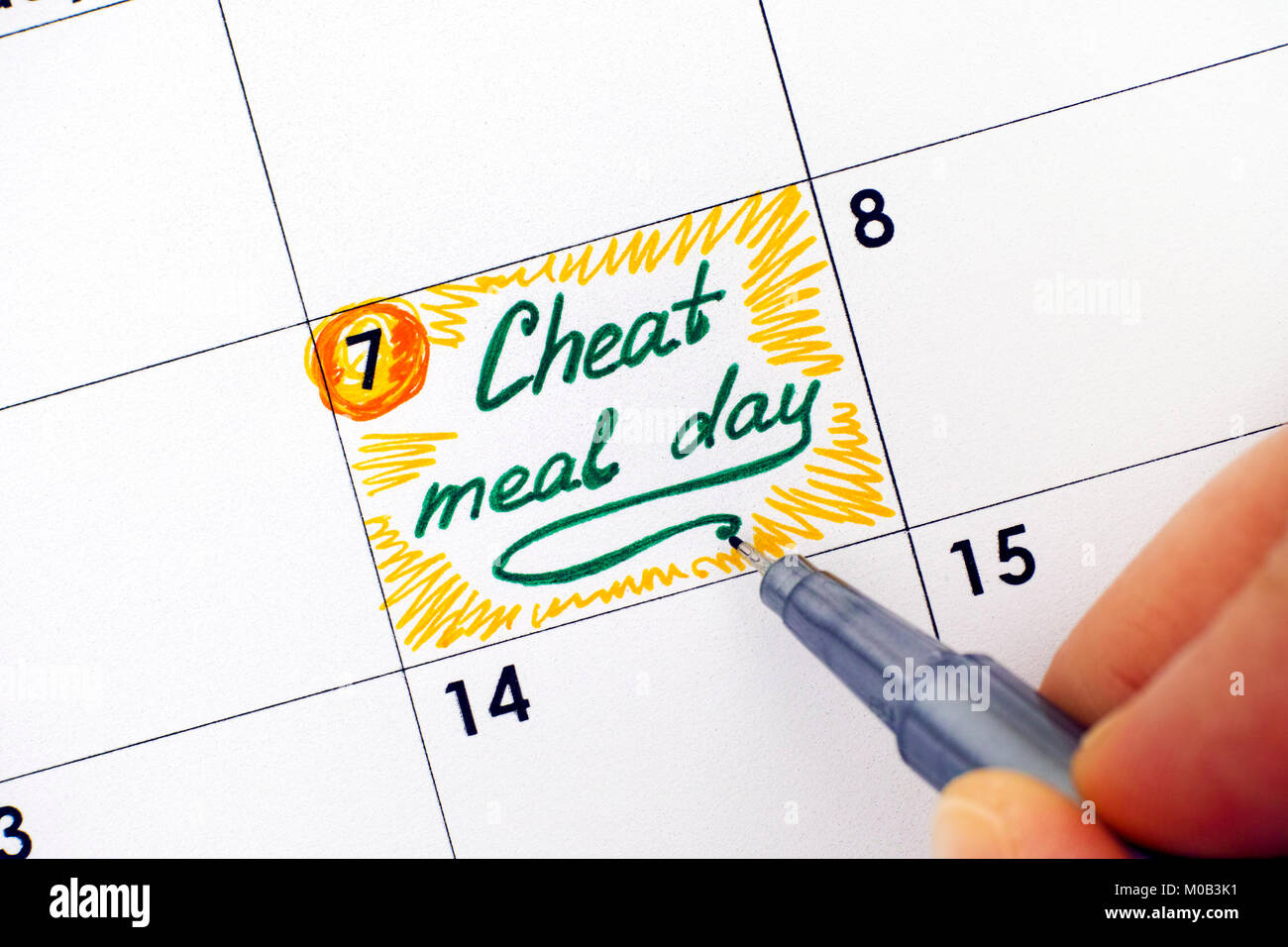 Woman hand with pen writing reminder Cheat Meal Day in calendar. Close-up. - Stock Image