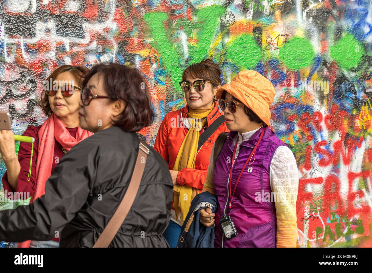 Chinese tourists posing for photographs in front of the Graffiti covered  John Lennon Wall in Prague . - Stock Image