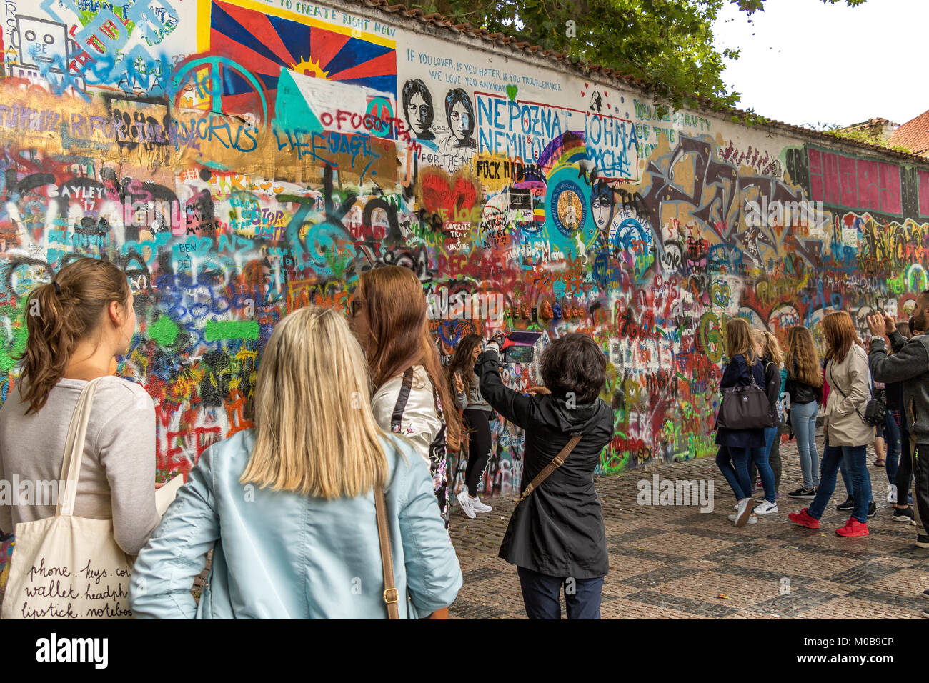 Tourists posing for photographs and looking at the  Graffiti which covers   John Lennon Wall in Prague . - Stock Image