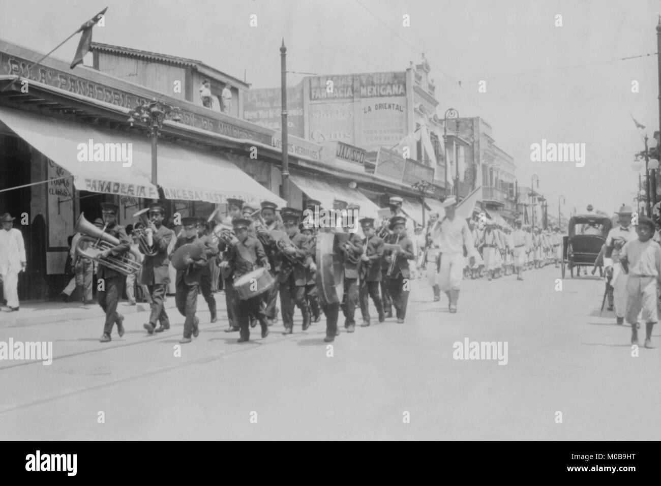 Mexican Band Plays Instruments in front of Marching Columns of U.S. Navy Sailors - Stock Image