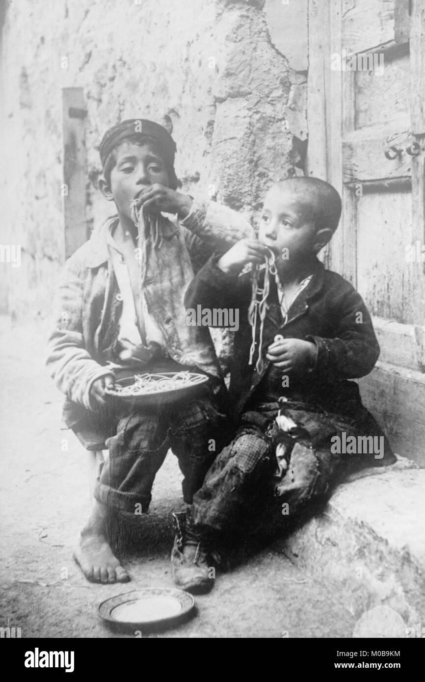 Two Neapolitan Children slurp down Spaghetti - Stock Image
