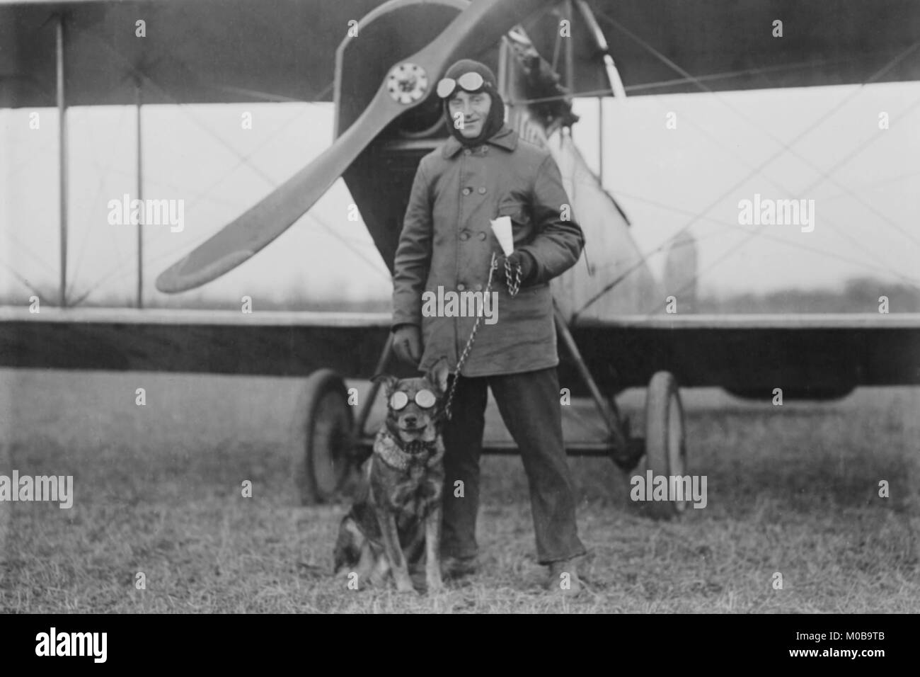 Aviator and His dog wear goggles in front of his Biplane - Stock Image