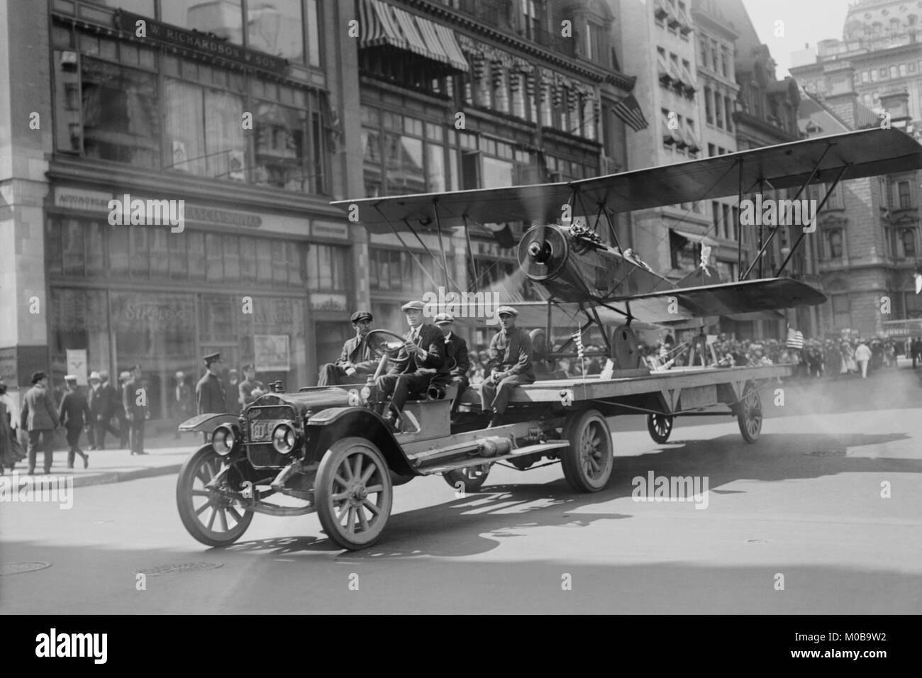 Biplane with spinning propeller is towed down Fifth Avenue New York for July 4th Parade - Stock Image
