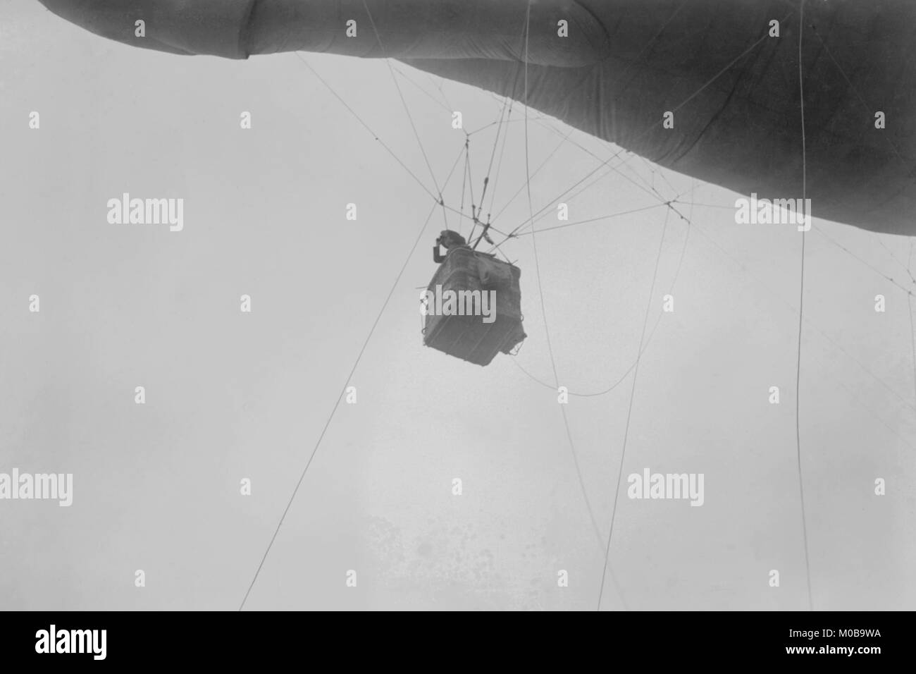 Military Observer hangs from a Balloon by guide wires looking over battlefield - Stock Image