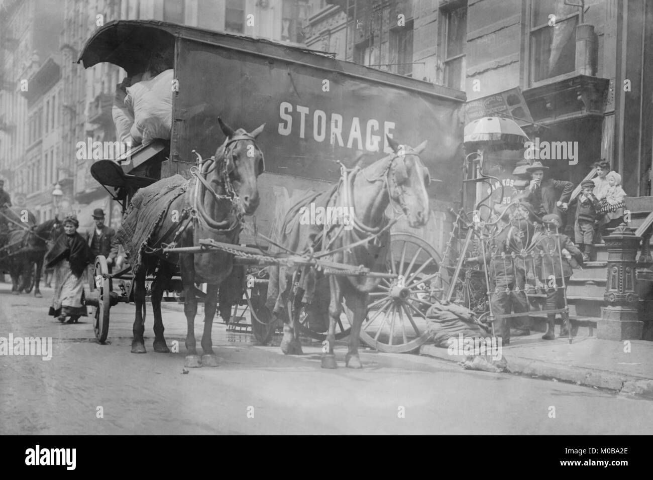 Horse Drawn Wagon with sign saying STORAGE unload the home content of a family being evicted - Stock Image