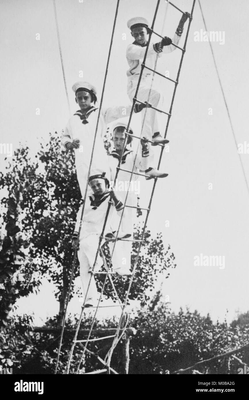 Crown Prince of Germany's Children frolic on what appears to be a ship's ratline or rope ladder - Stock Image