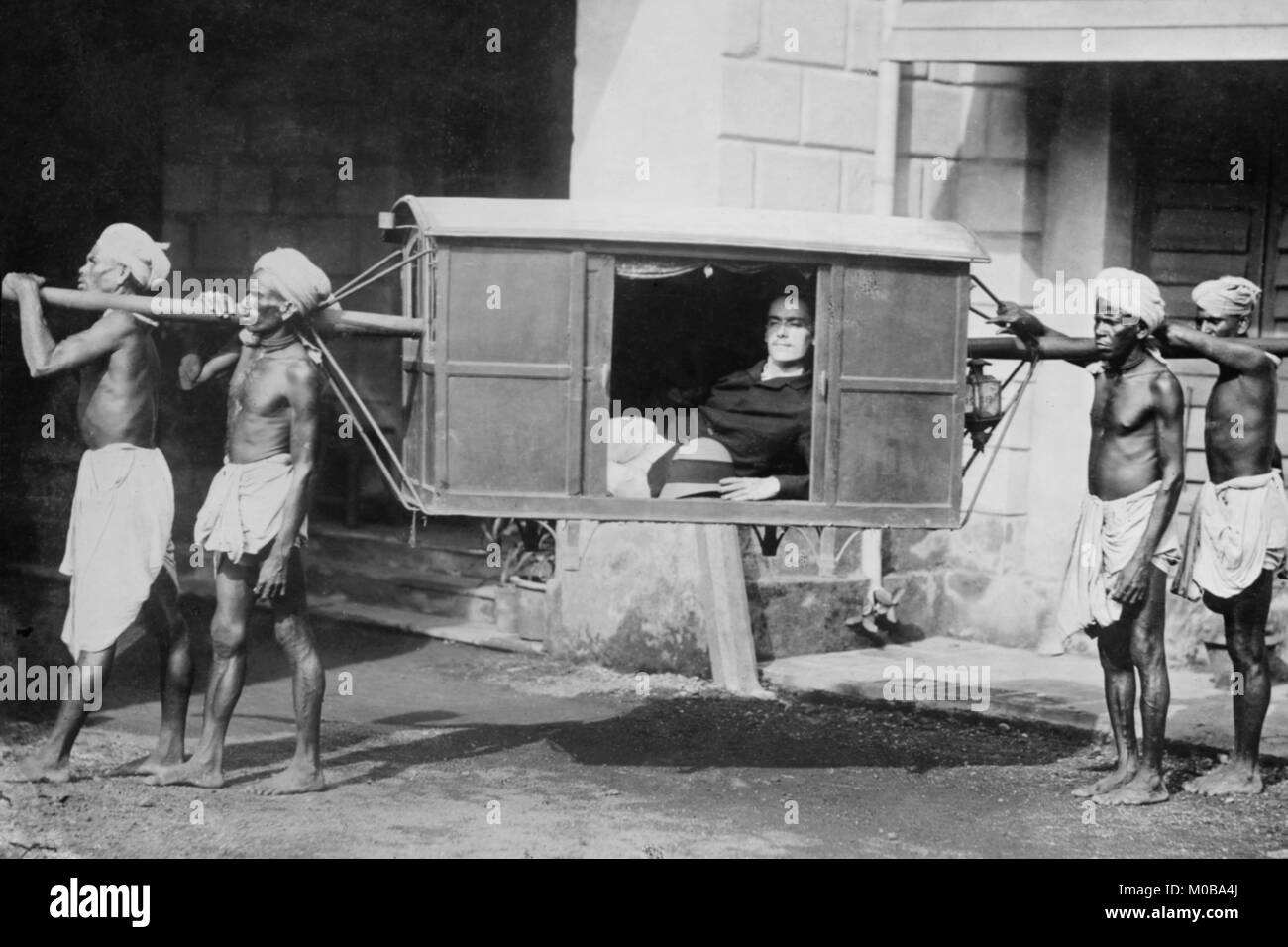 Four Indian Porters Carry a Westerner in a palanquin or Sedan Chair - Stock Image