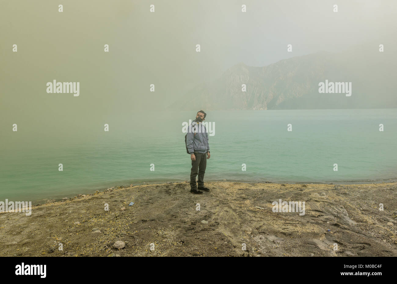 Tourist surrounded by toxic gas standing near Ijen crater lake, Indonesia - Stock Image