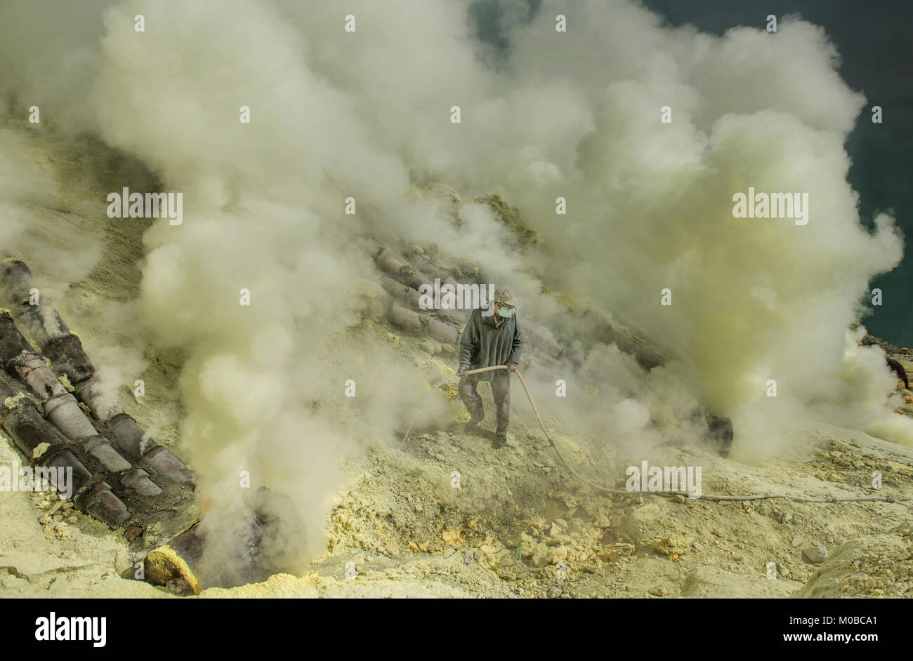 Ranger surrounded by toxic gas trying to put of the excess smoke from the pipe to enhances sulphur production  in - Stock Image