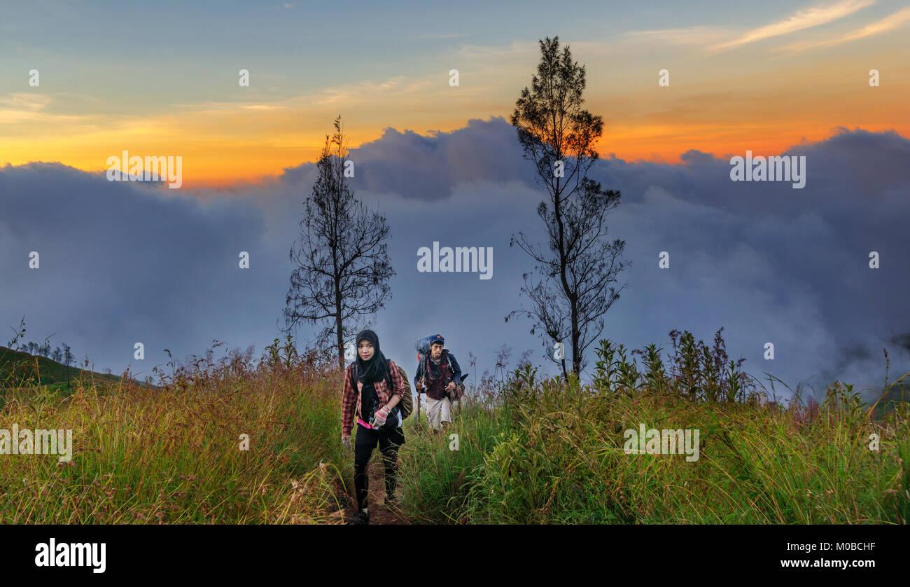 Couples trekking mountain to reach summit, Rinjani, Indonesia - Stock Image