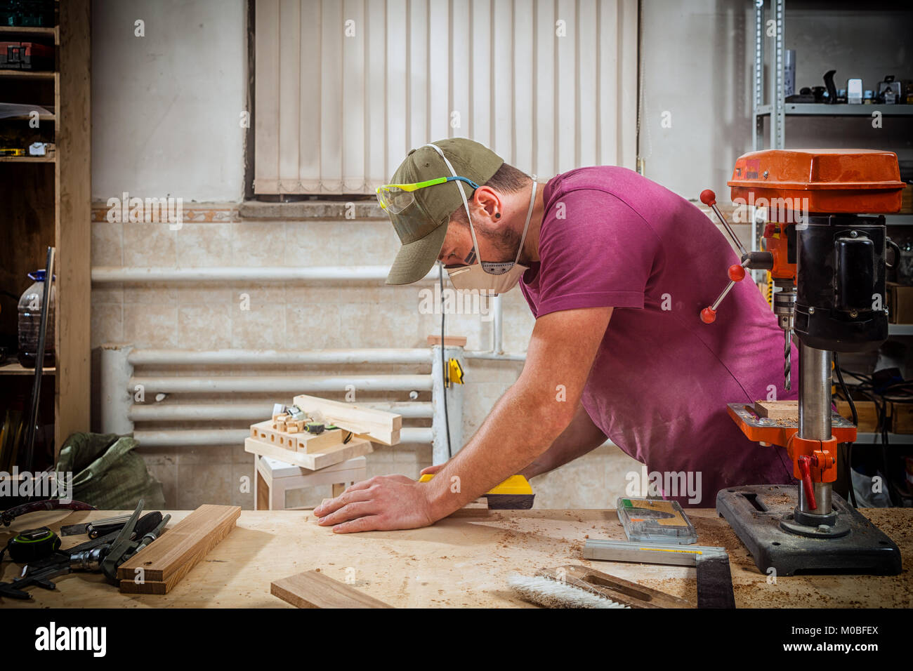 A young strong man builder carpenter works with a wooden bar for making furniture, measures and cuts in the workshop, Stock Photo