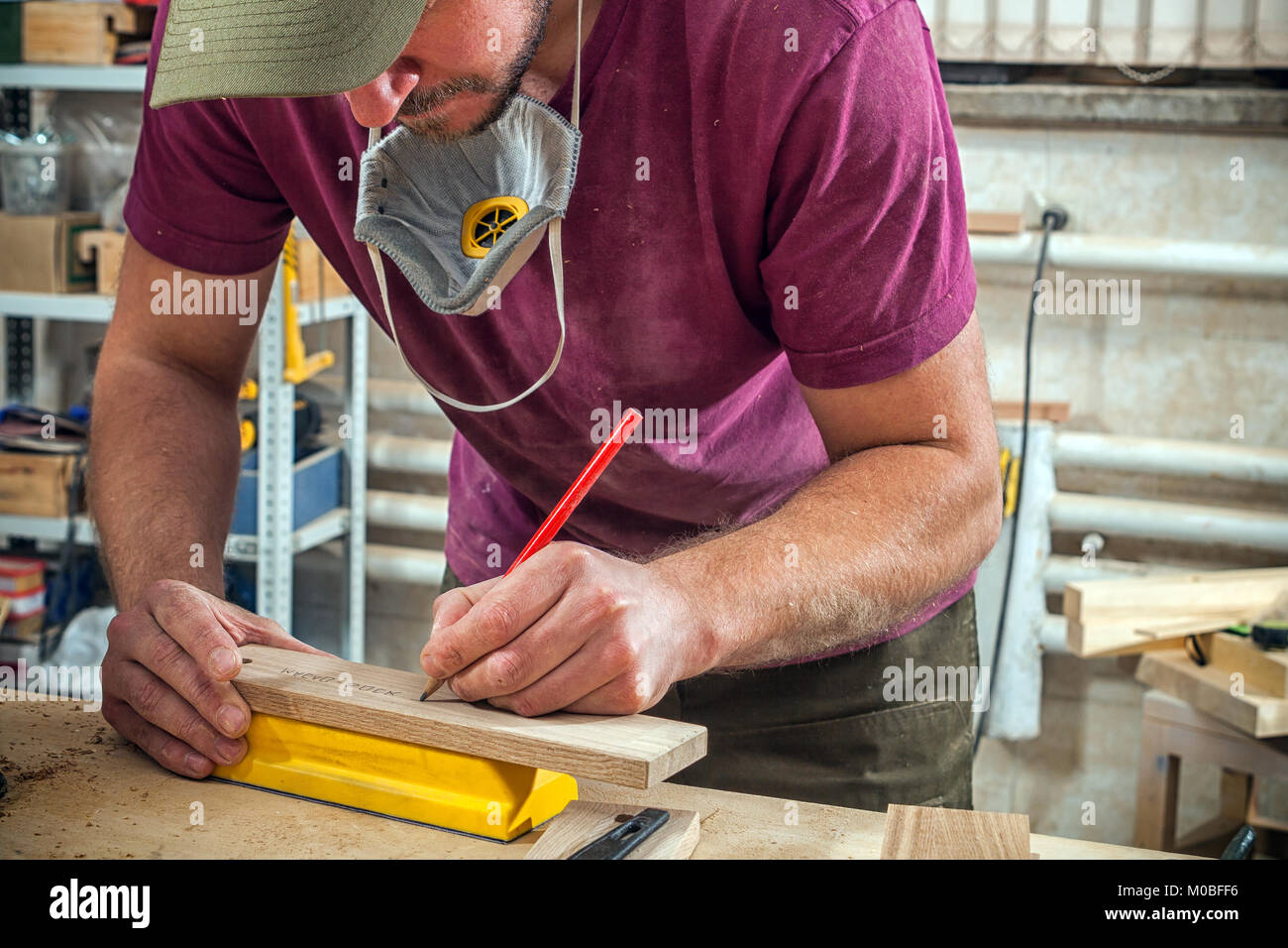 A young strong man builder carpenter works with a wooden bar for making furniture, measures and cuts in the workshop, - Stock Image