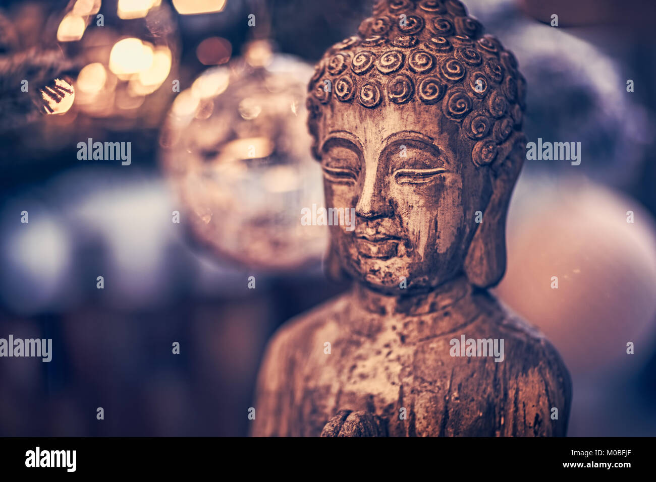 Vintage style photo of the wooden statue of Buddha, God of oriental religion, conceptual picture of meditation, - Stock Image