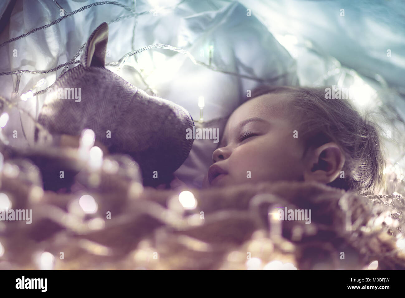 Sweet little baby boy sleeping with favourite soft toy, dreaming at home on magic night, vintage style fantasy photo Stock Photo