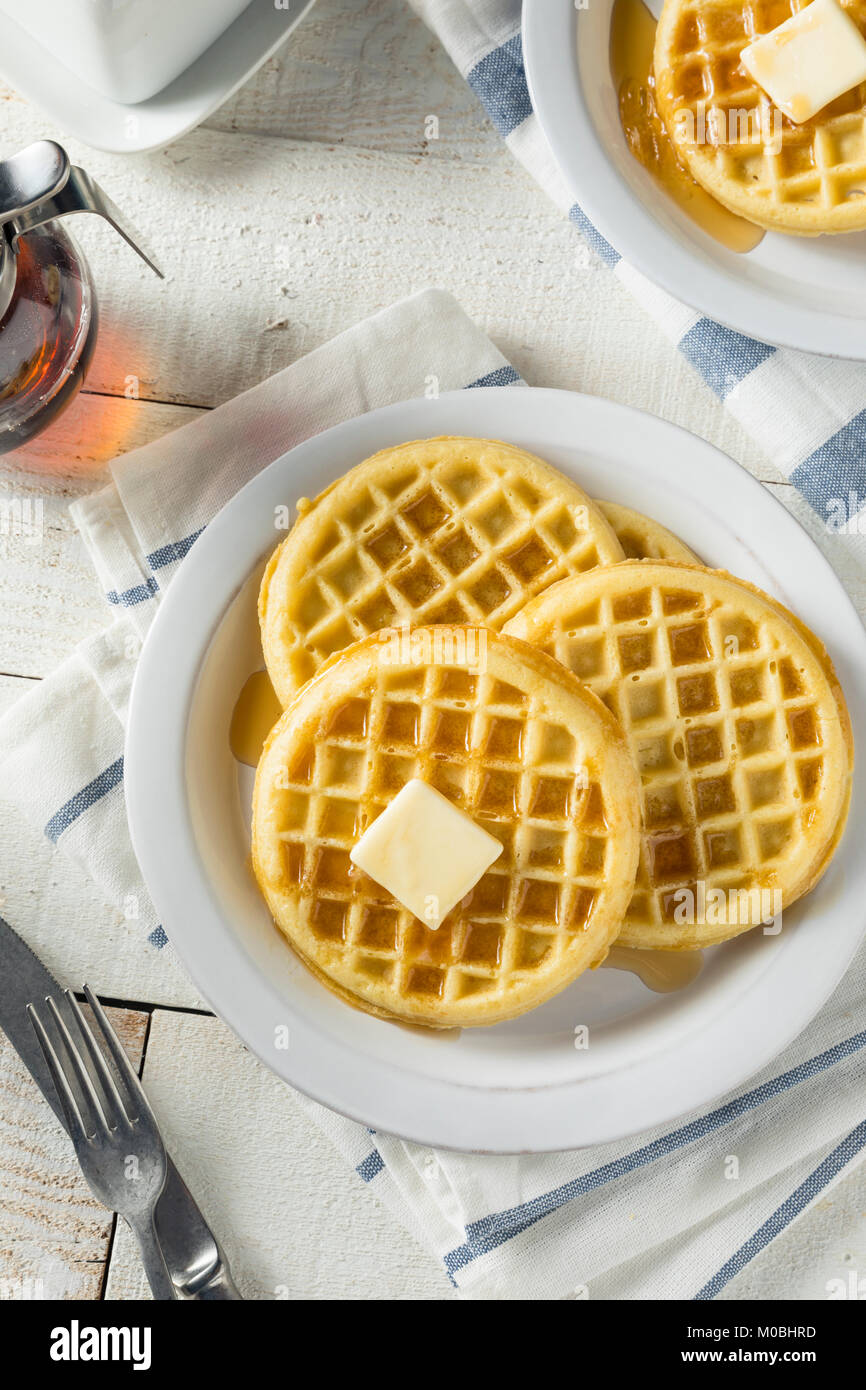 Brown Hot Freezer Waffles with Butter and Maple Syrup - Stock Image