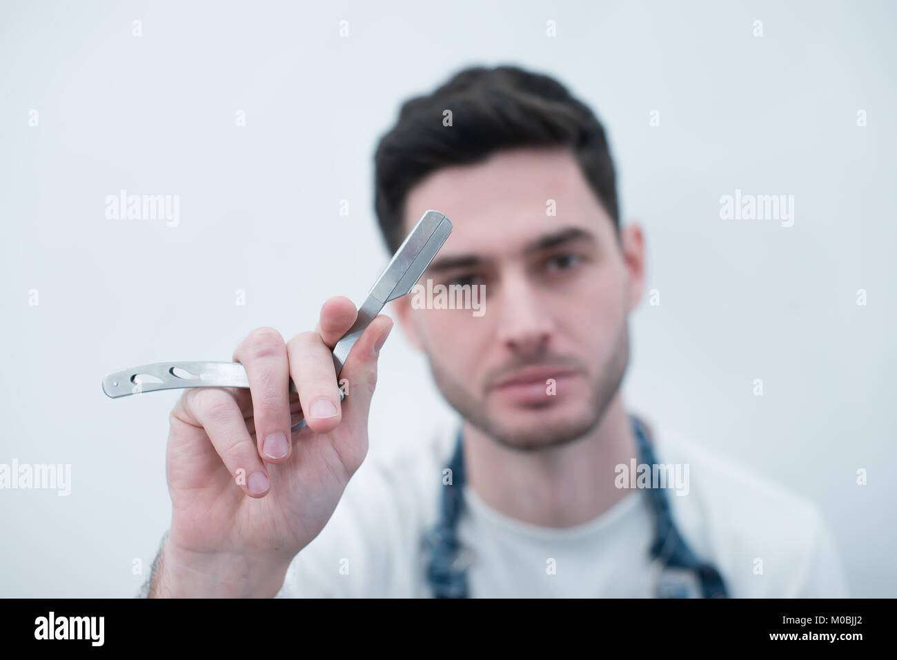 Barber keeps the razor against the background of a white wall. Bearded brutal young man with tools in his hands. - Stock Image