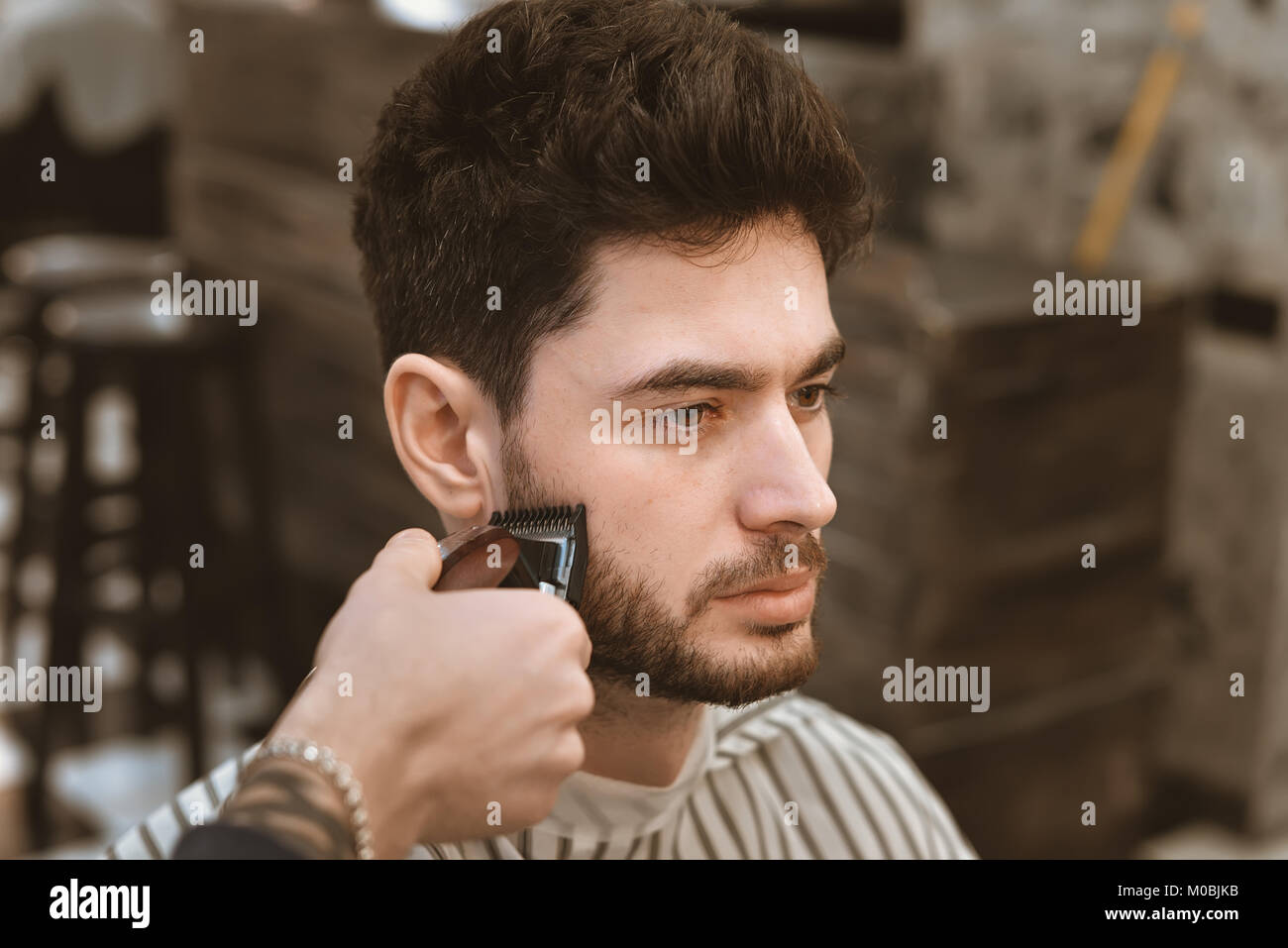 The hands of young barber making haircut to attractive man in barbershop - Stock Image