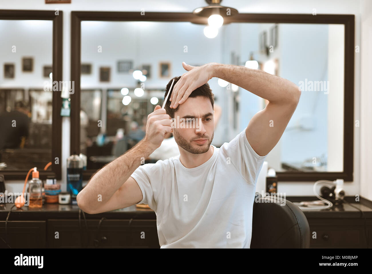 Working process in modern barbershop. Handsome hairdresser serving customer, styling hair for male client using - Stock Image