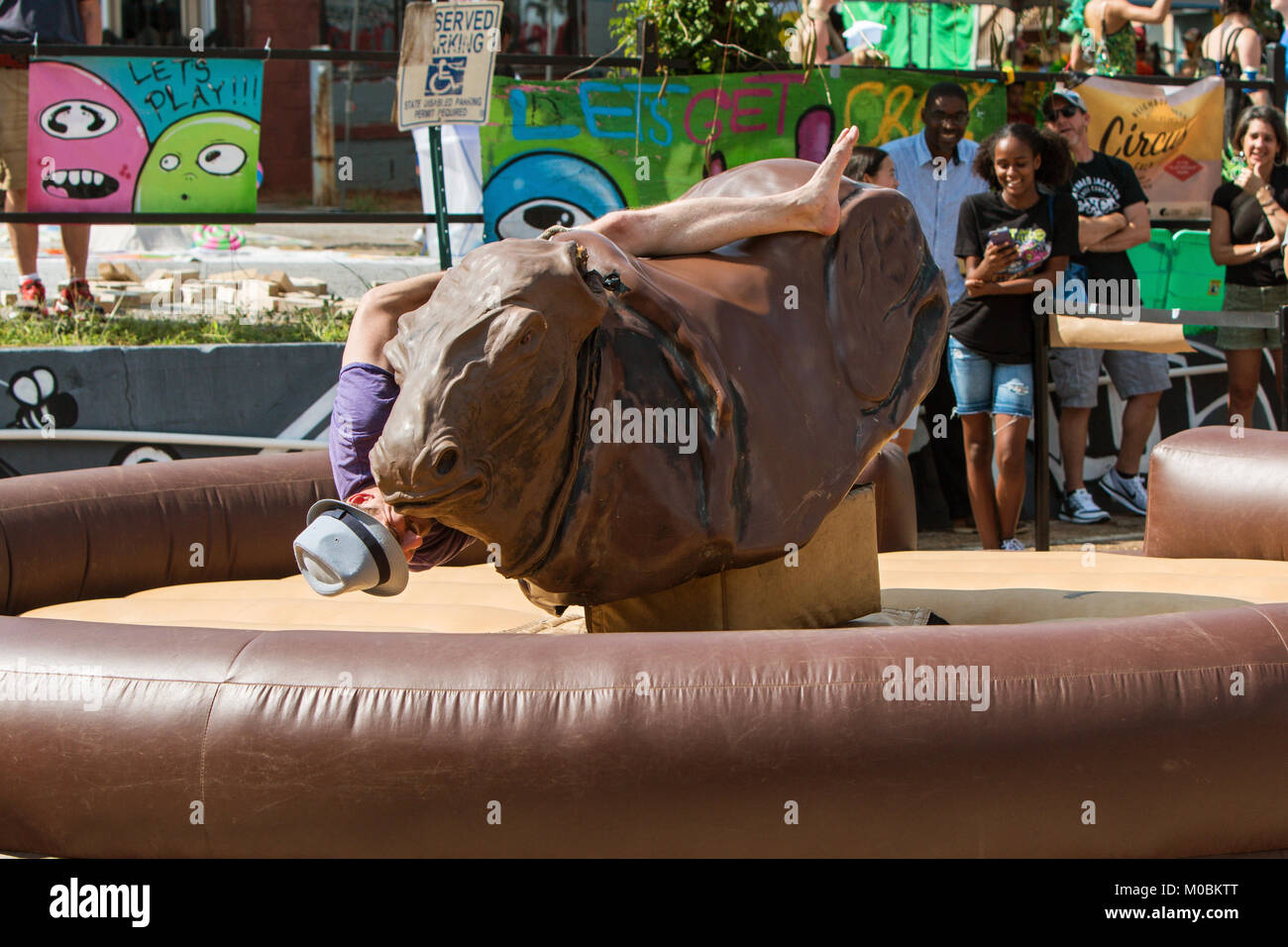 Atlanta, GA, USA - September 23, 2017:  A young man desperately tries to stay on a mechanical bull as he starts - Stock Image