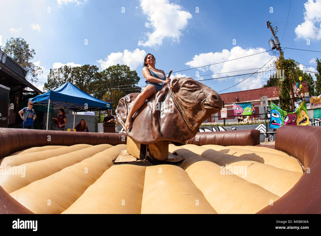 Atlanta, GA, USA - September 23, 2017:  A young woman tries to stay upright as she rides a mechanical bull at the - Stock Image