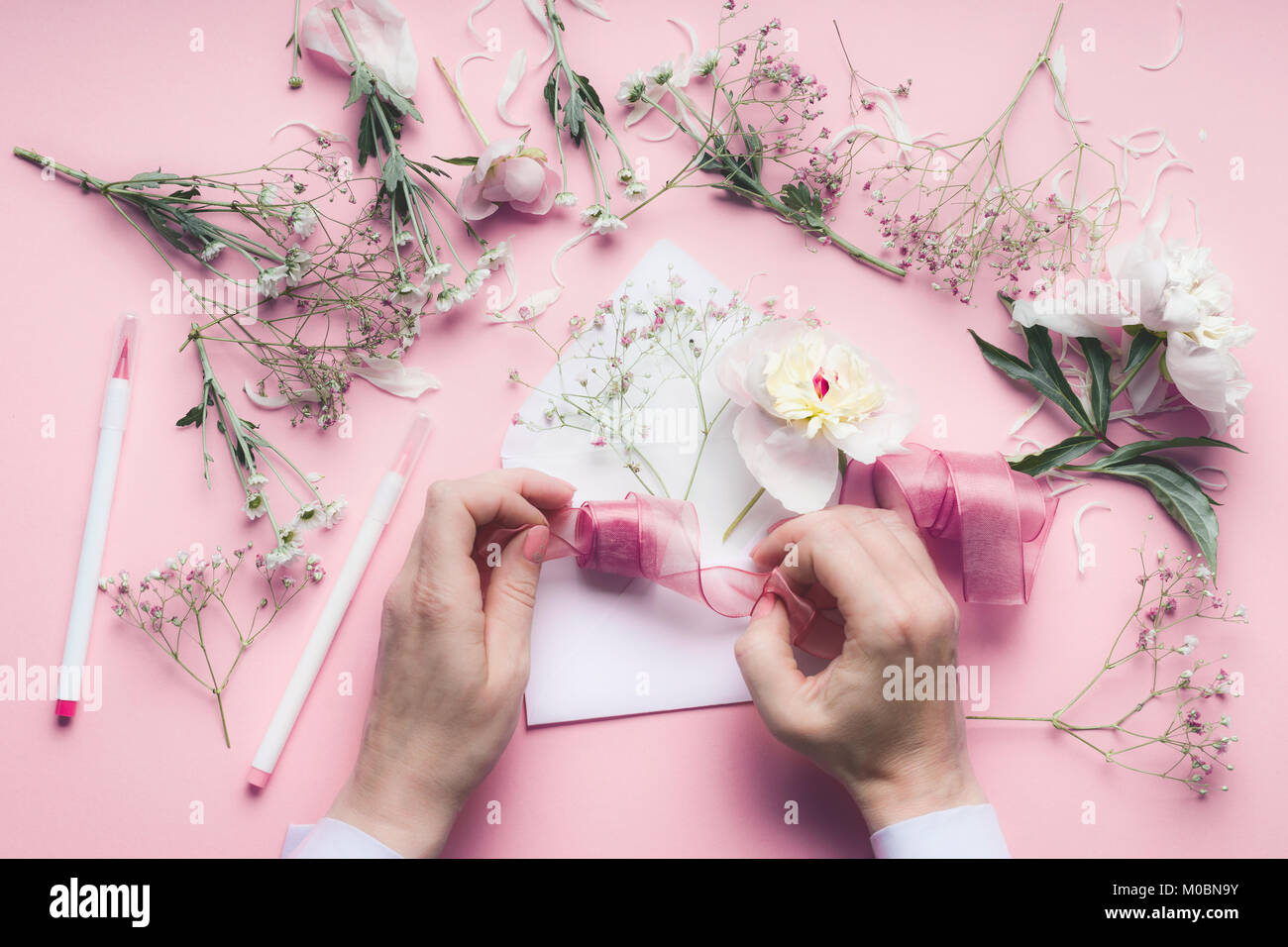 Female Hand Making Greeting Card With Envelope With Flowers