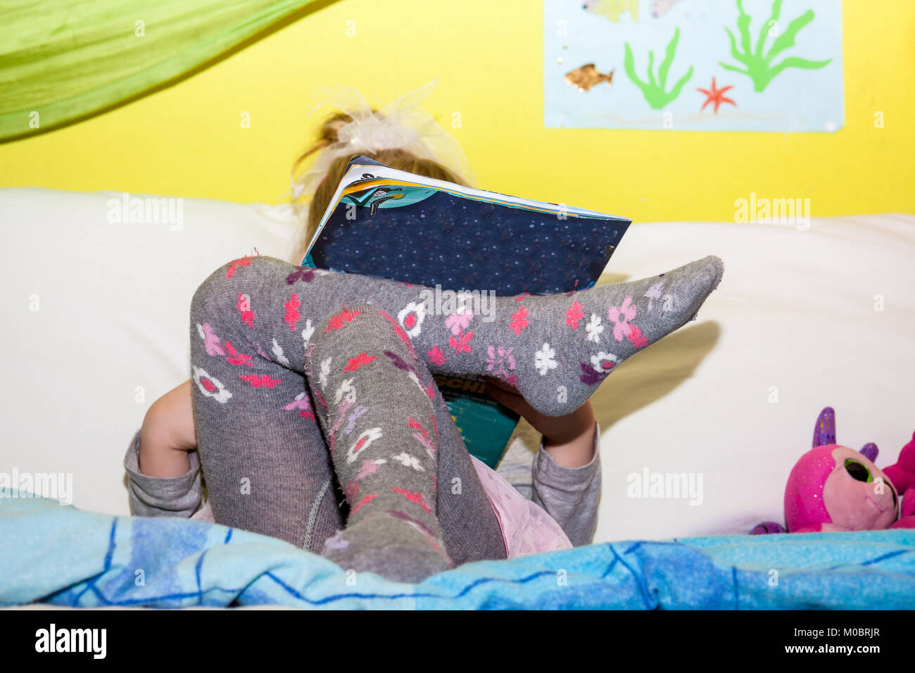 Little girl reading colourful book with pictures and text - Stock Image