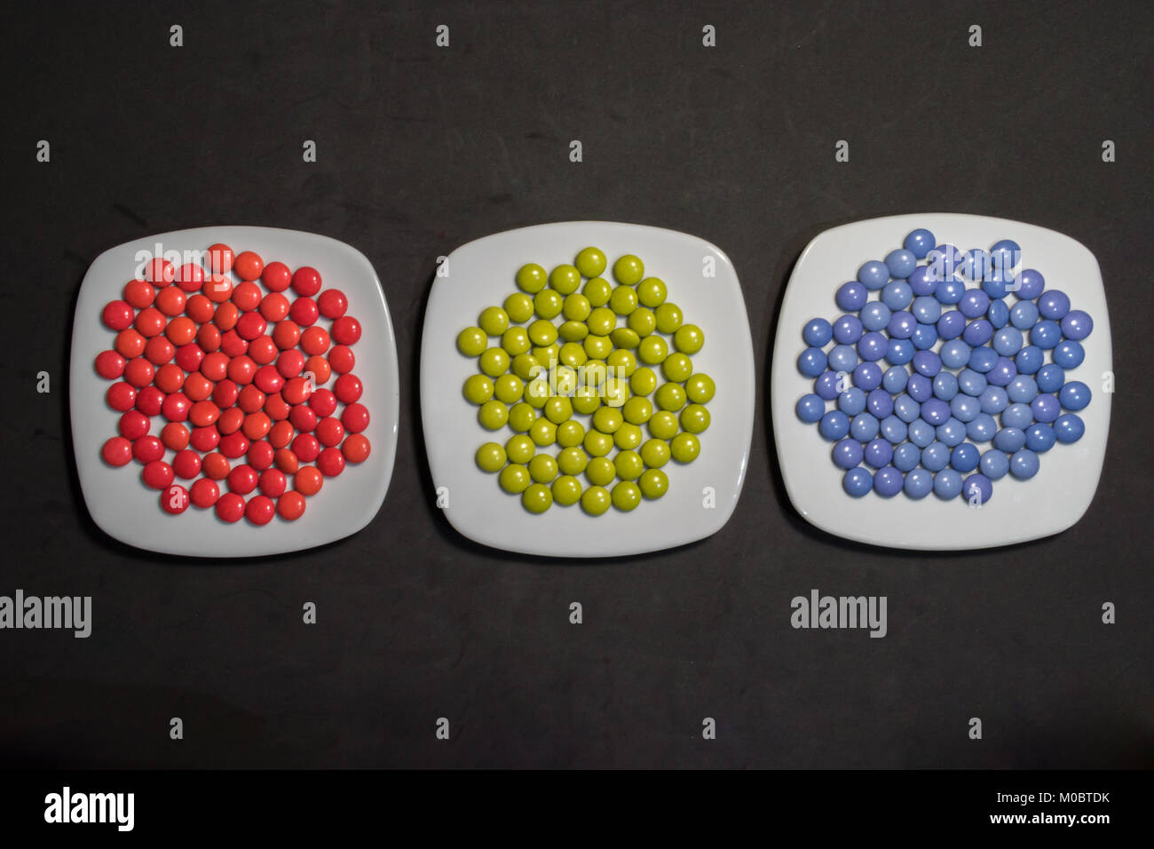 Three plates with colorful candies of chocolates with RGB colors on black background - Stock Image