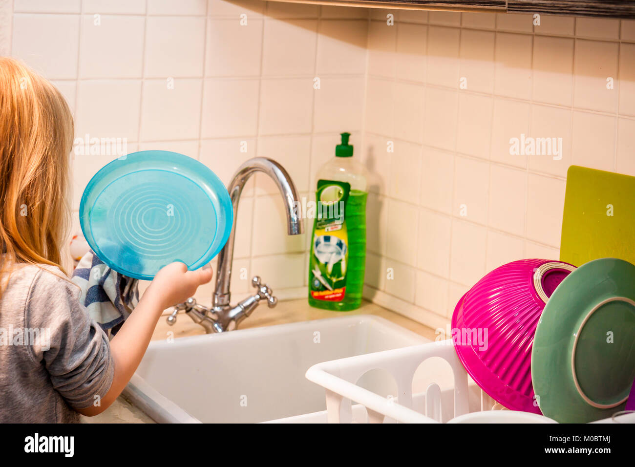 Girl in the kitchen with a plate and towel doing the wash up - Stock Image