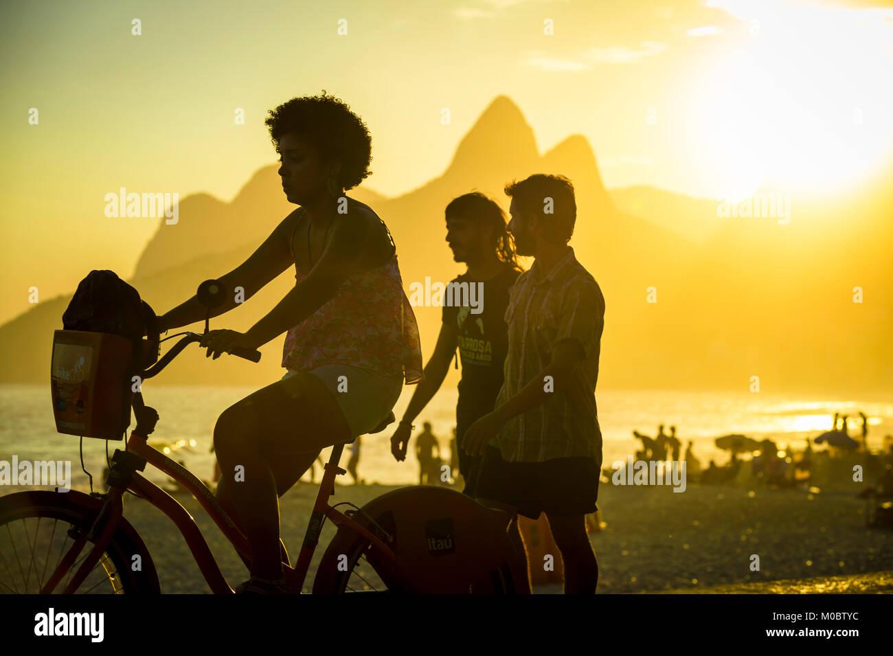 RIO DE JANEIRO - MARCH 20, 2017: Visitors pass along Ipanema Beach to Arpoador, a popular spot to take in the sunset - Stock Image