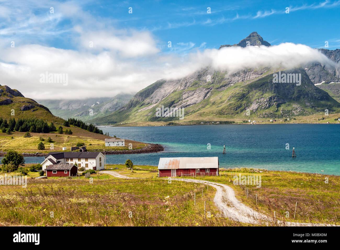 Traditional farm buildings in coast landscape on Lofoten islands in northern Norway. Lofoten is a popular tourist - Stock Image