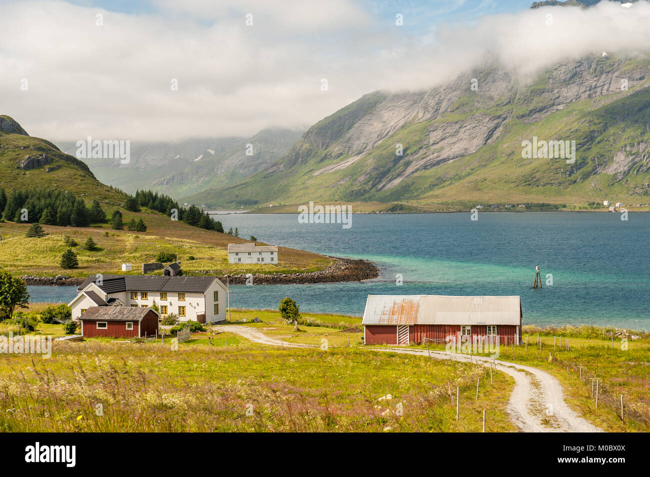 Traditional farm buildings in coast landscape on Lofoten islands in northern Norway. Lofoten is a popular tourist Stock Photo