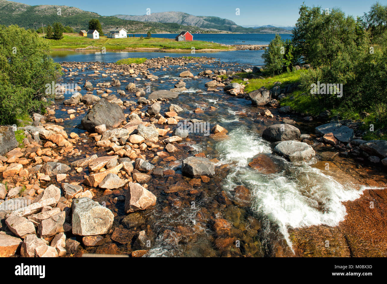 Creek flowing out in the sea at Lofoten in northern Norway during summer time. - Stock Image