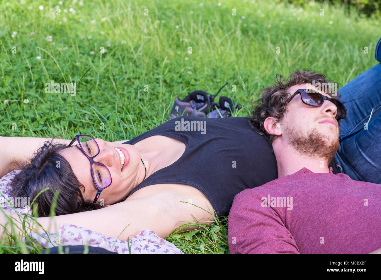 Young couple lying down on lush green grass in park, relaxing, embracing. Real people, natural color. Conpept of - Stock Image