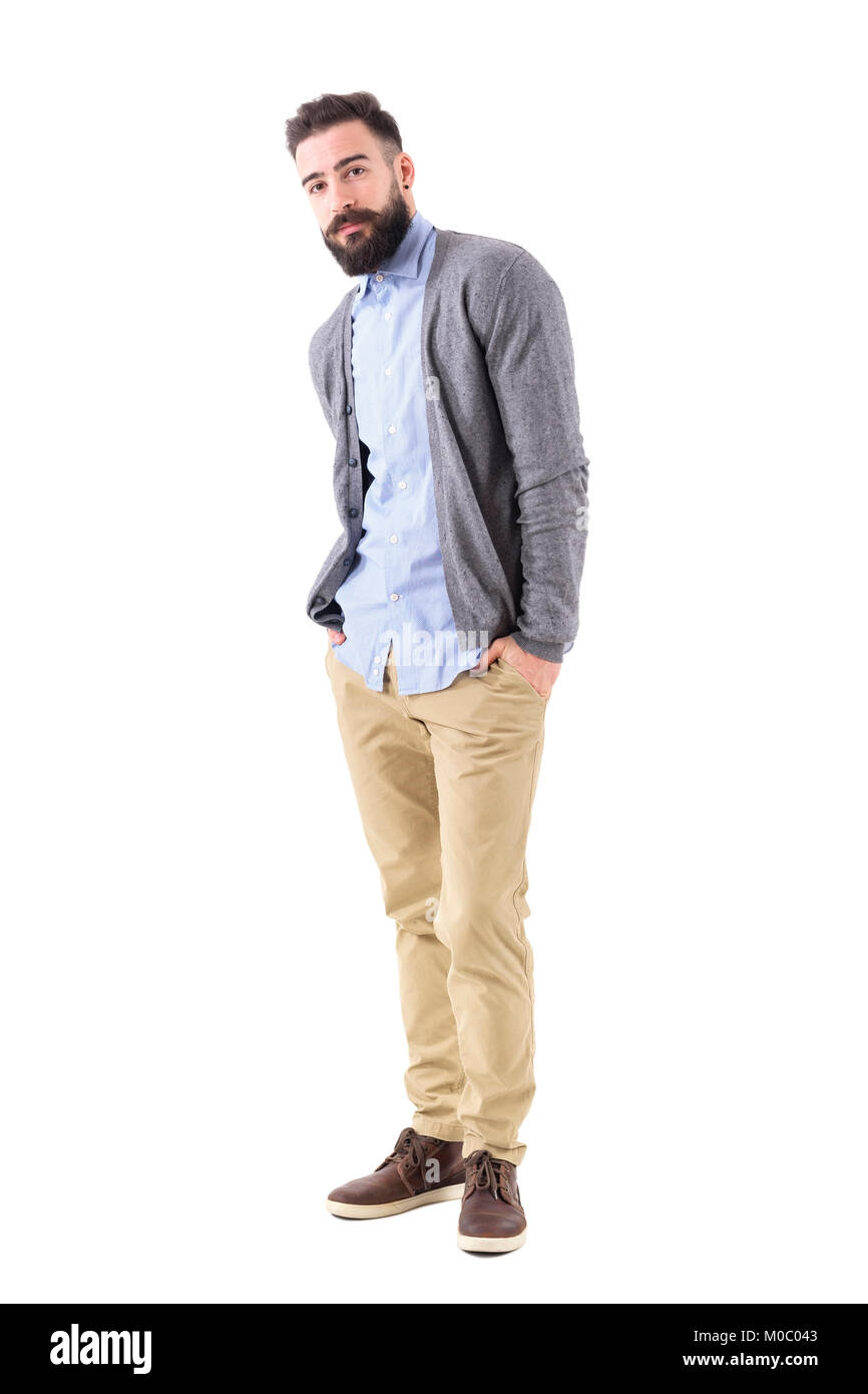 Handsome hipster in smart casual clothes posing tilted with hands in pockets. Full body length portrait isolated - Stock Image