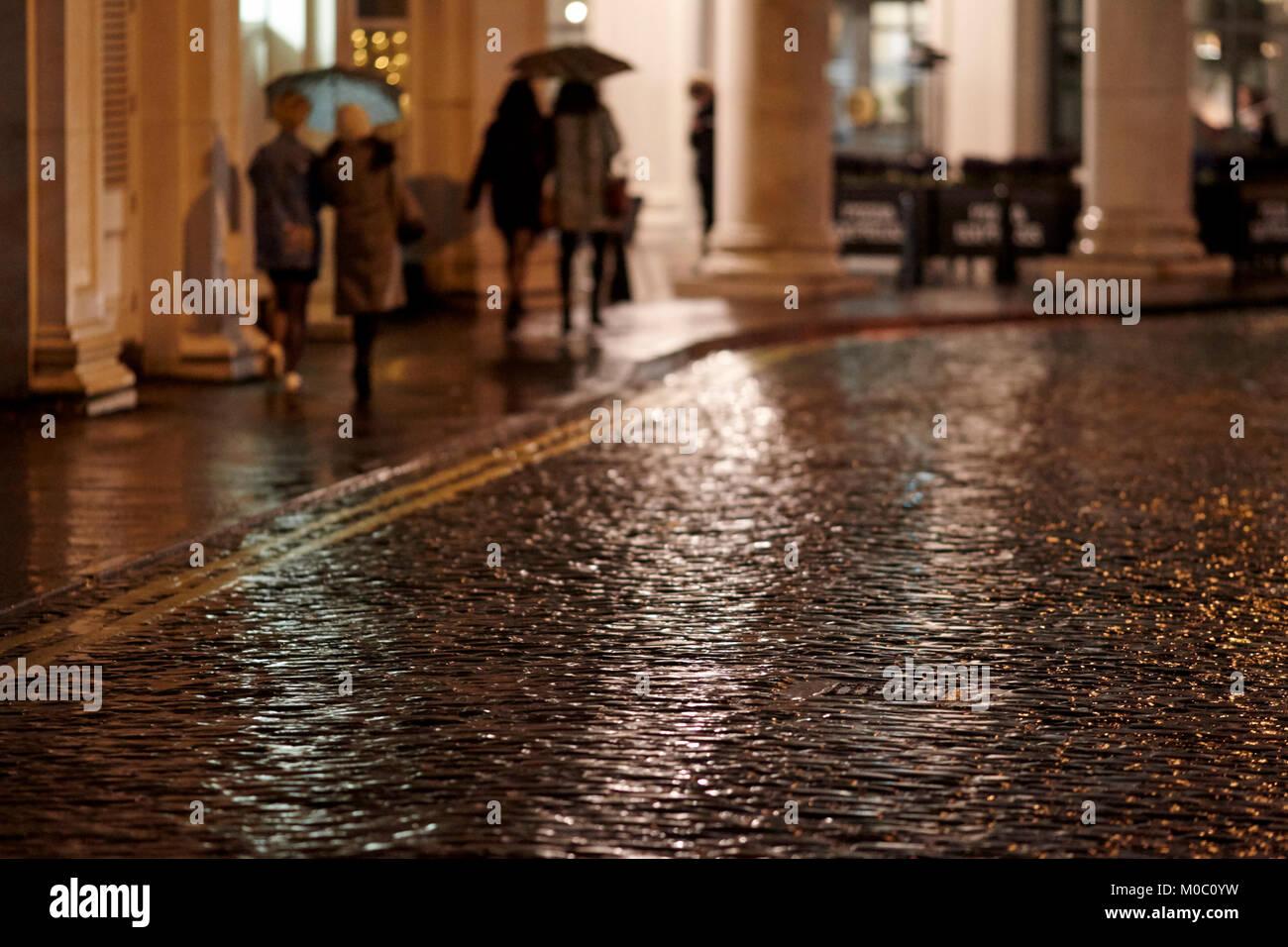 women walking at night on path near wet cobblestoned street at night belfast northern ireland uk - Stock Image