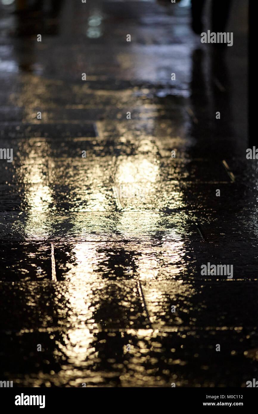 light reflecting on wet pavement in urban pedestrianised area belfast northern ireland uk - Stock Image