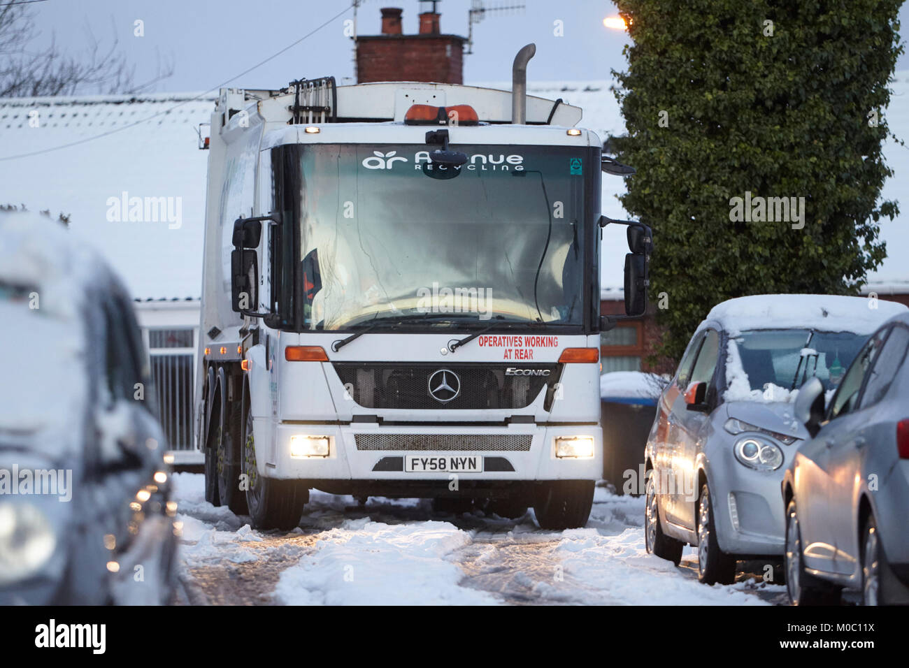 mercedes econic refuse recycling collection truck driving along street covered in snow in newtownabbey northern - Stock Image