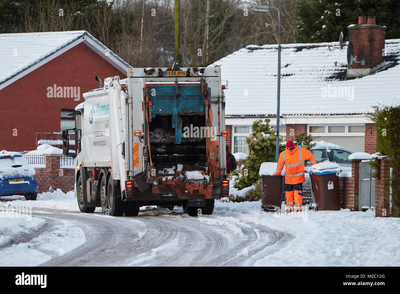 worker collecting bins with refuse recycling collection truck driving along street covered in snow in newtownabbey - Stock Image