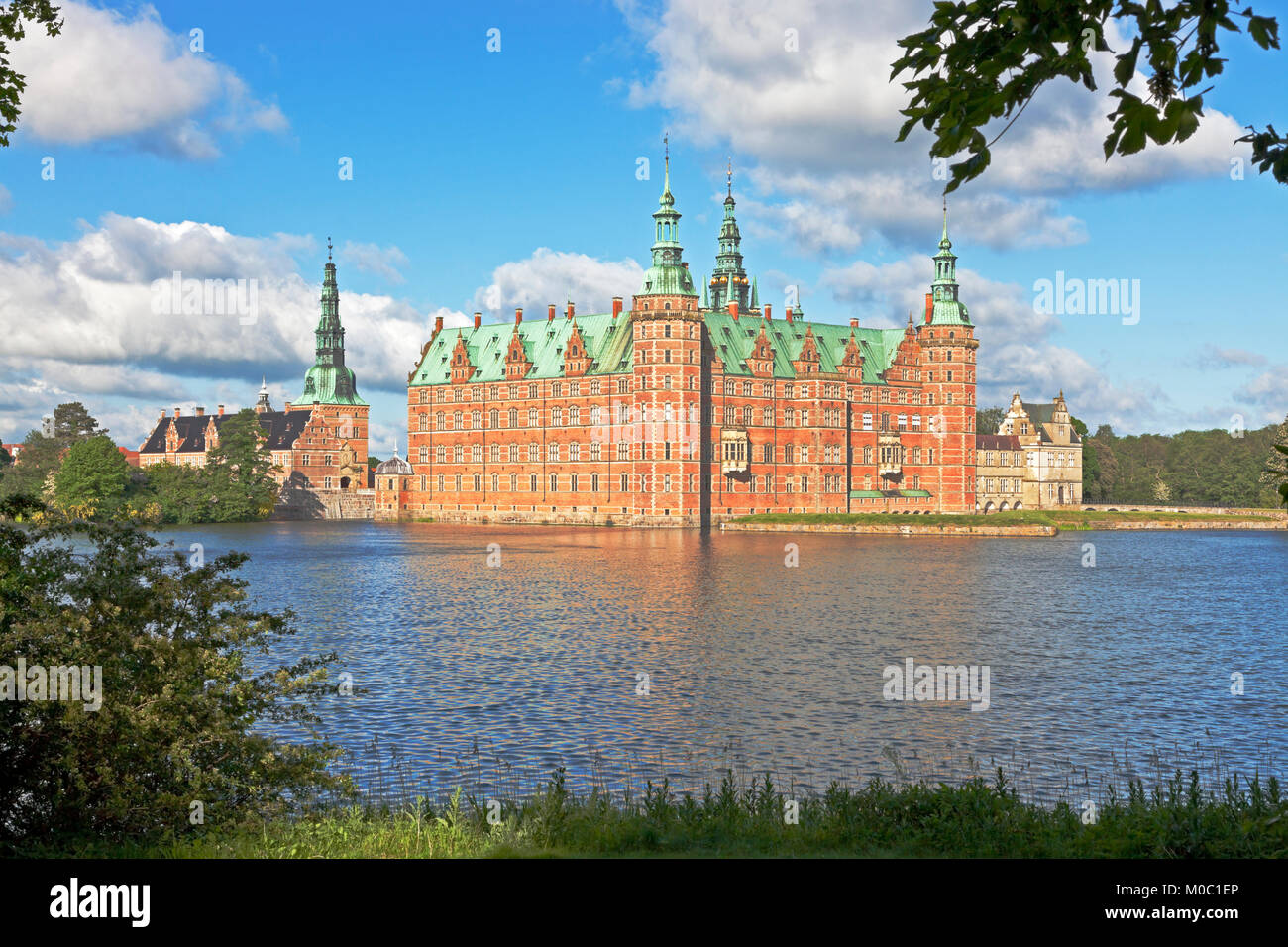 The Frederiksborg Castle in Dutch Renaissance style in Hillerød, North Sealand, Denmark, in bright summer morning sunshine seen through spring leaves. Stock Photo