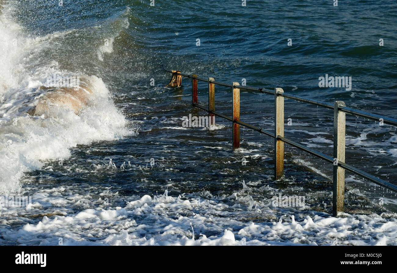 Seafront railings disappearing into the sea at high tide. - Stock Image