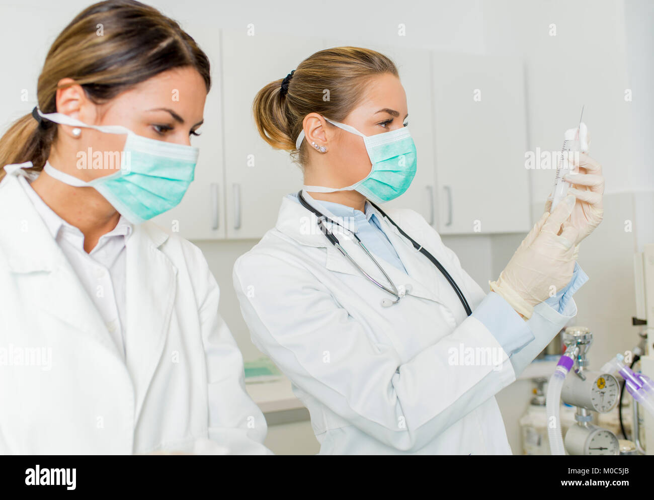 Side view at female doctors with injection - Stock Image