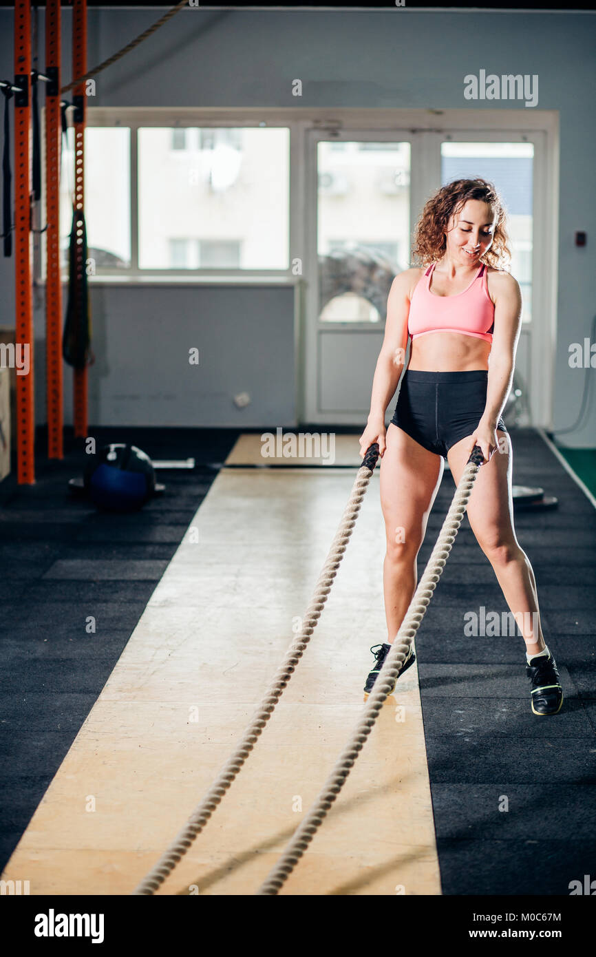 Athletic young woman doing some cross fit exercises with rope outdoor - Stock Image