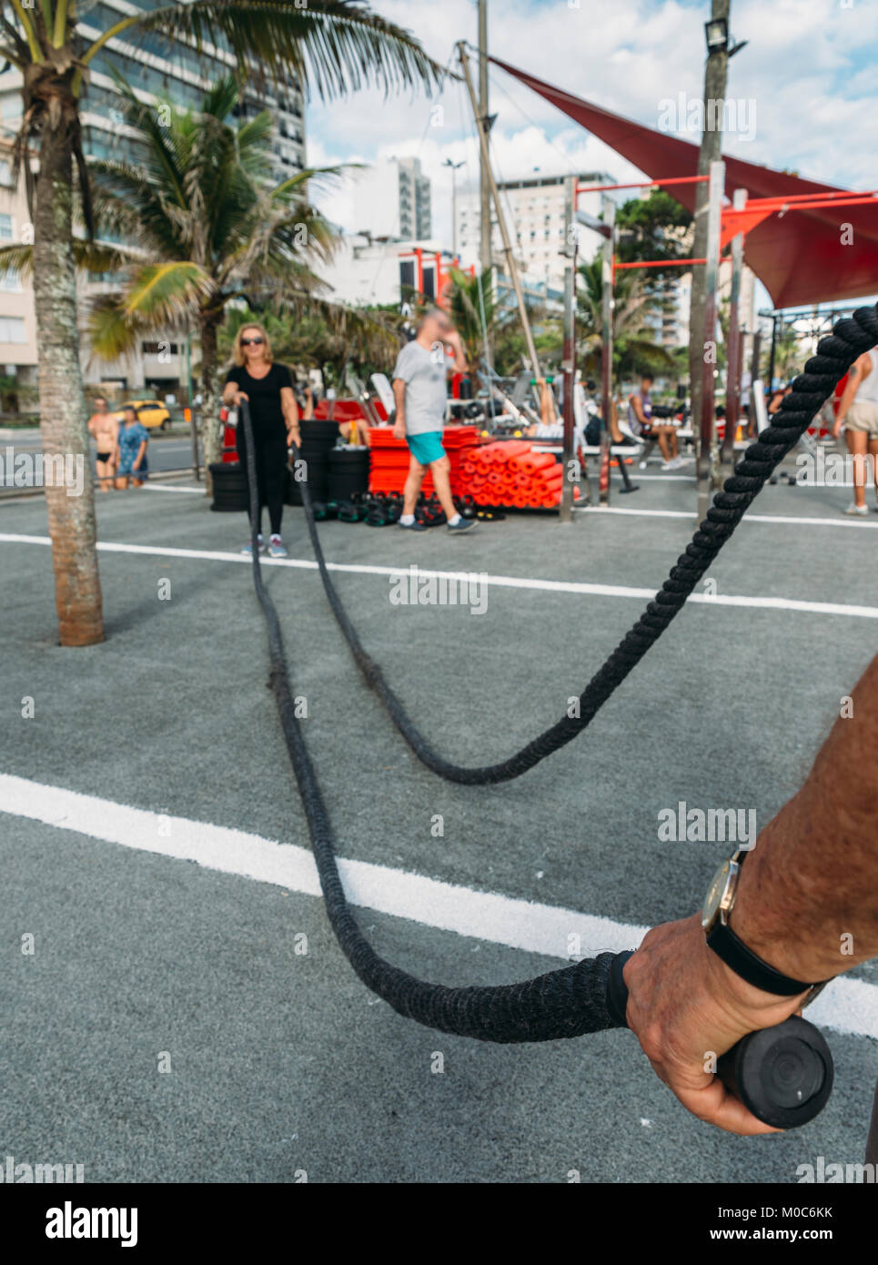 Model Released: Man holding battling rope with older woman (70-79) on background at public gym in Ipanema, Rio de - Stock Image