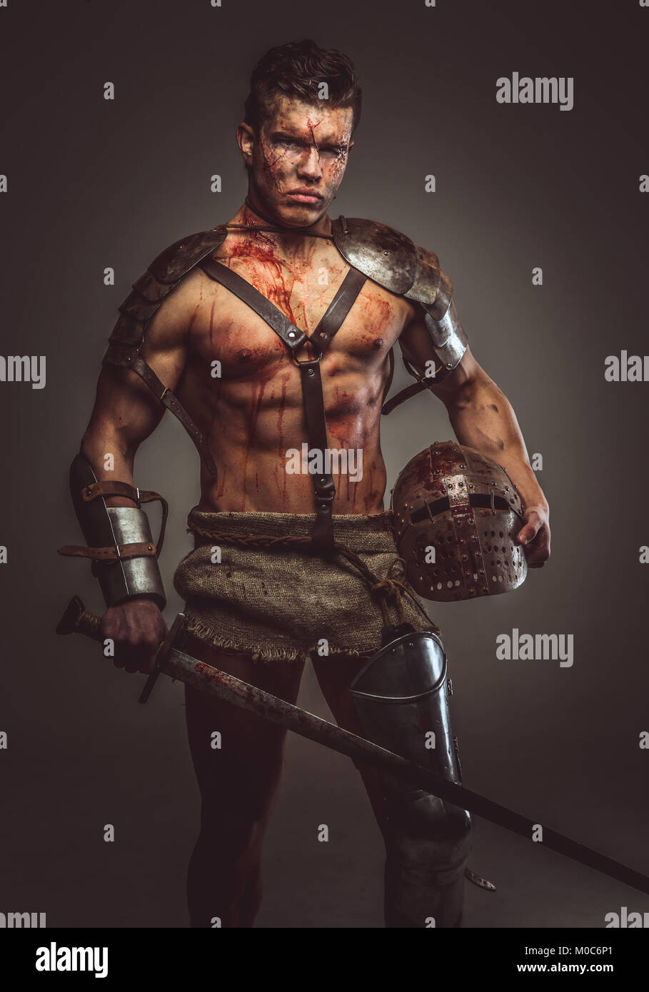 Muscular bloody gladiator with sword and helmet. - Stock Image