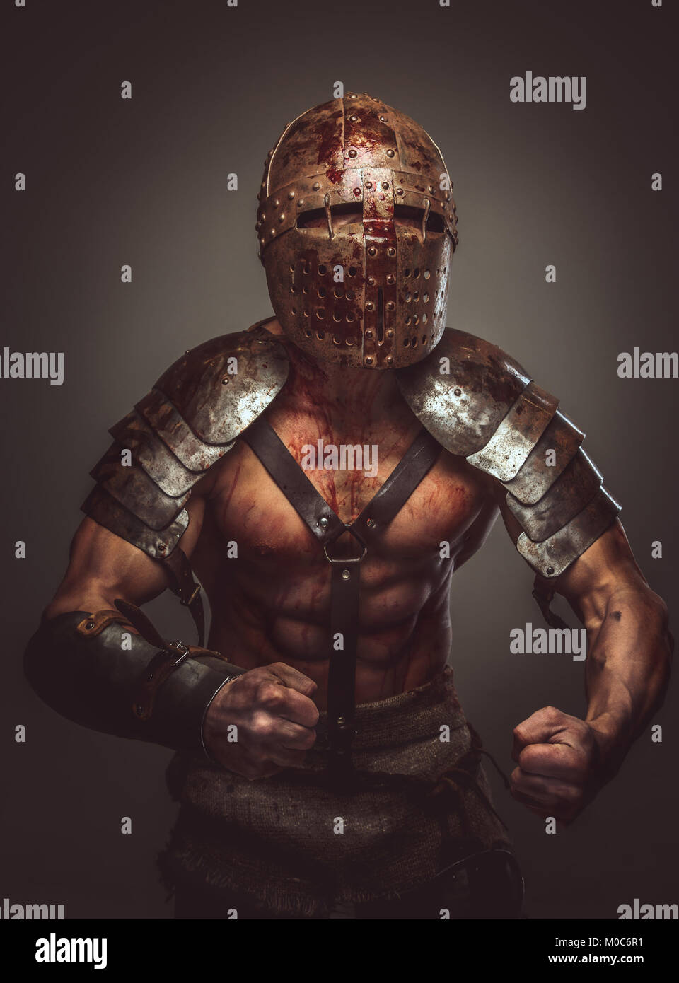 Angry bloody gladiator in helmet and ancient armor. - Stock Image