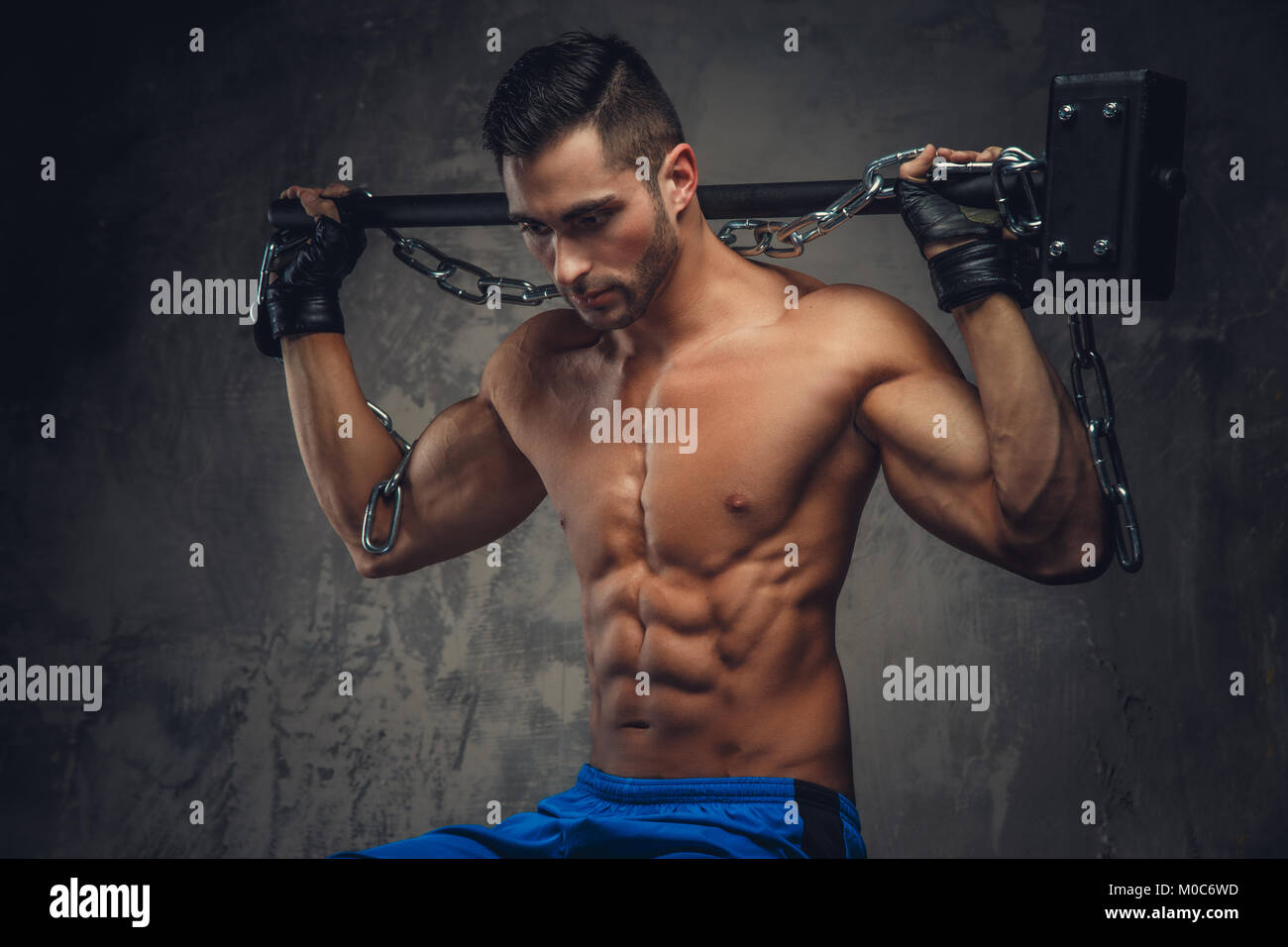 Athletic guy holding a hammer. - Stock Image