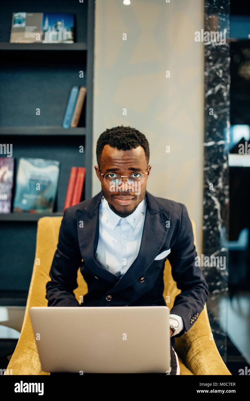 Employee wearing suit working online on laptop - Stock Image