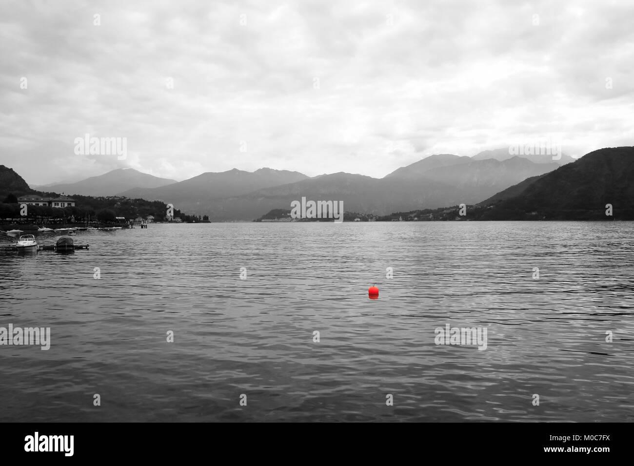 Einsames Segelboot mit einer roten Boje am Comer See in Italien, bei Lenno - Stock Image