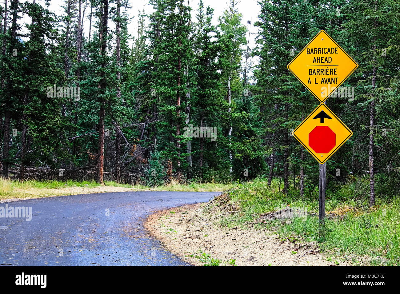 A Stop and Barricade Ahead sign along a road - Stock Image